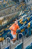sportive young man jogging upstairs at sports stadium