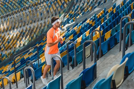 athletic young man jogging upstairs at sports stadium