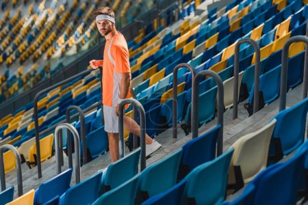 sportive young man walking downstairs on stairs at sports stadium