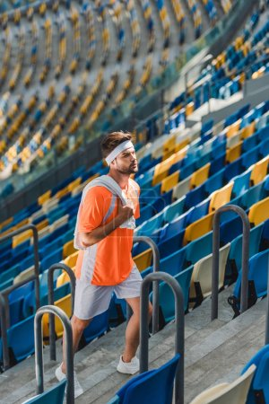 sportive young man walking upstairs on stairs at sports stadium