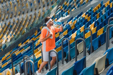 tired young sportsman drinking water on stairs at sports stadium