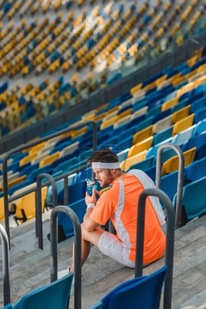tired young sportsman sitting on stairs at sports stadium with bottle of water