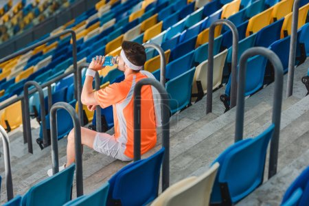 tired young sportsman drinking water while sitting on stairs at sports stadium