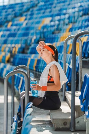 side view of tired young woman relaxing on stairs and wiping sweat at sports stadium