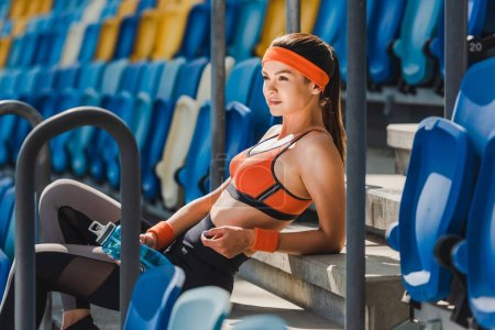 side view of happy young woman relaxing on stairs at sports stadium