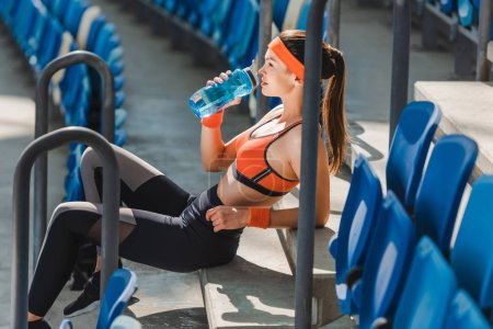 side view of tired young woman drinking water on stairs at sports stadium
