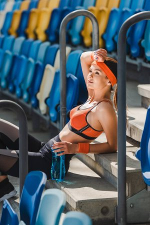 side view of tired young woman relaxing on stairs at sports stadium