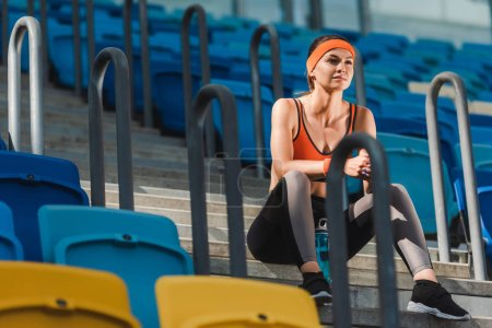 bottom view of beautiful young woman sitting on stairs at sports stadium