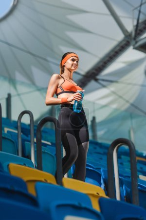 bottom view of beautiful young woman walking on stairs at sports stadium