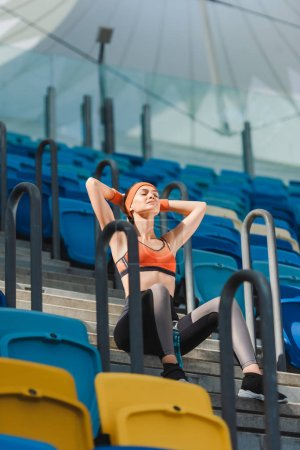 bottom view of beautiful young woman relaxing on stairs at sports stadium