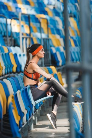 side view of attractive young woman sitting on tribunes at sports stadium