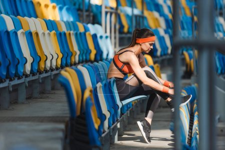 side view of sportive young woman sitting on tribunes at sports stadium