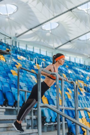 attractive young woman doing push ups on tribunes at sports stadium