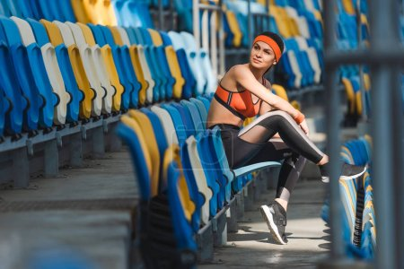 side view of beautiful young woman sitting on tribunes at sports stadium