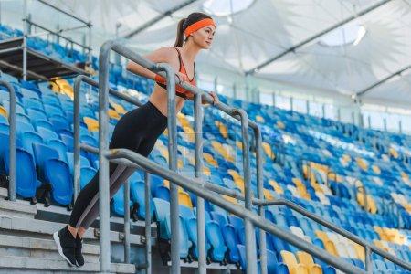beautiful young woman doing push ups on tribunes at sports stadium