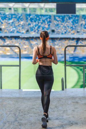 rear view of young woman jogging at sports stadium