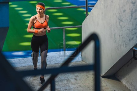 high angle view of beautiful young woman jogging at sports stadium