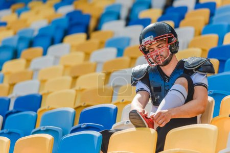 handsome young american football player sitting on tribunes at sports stadium and lacing up shoes