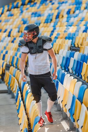 serious young american football player standing on tribunes at sports stadium