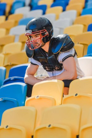 handsome young american football player sitting on tribunes at sports stadium