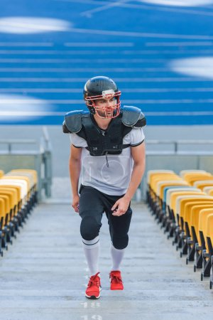 attractive young american football player going upstairs at sports stadium