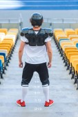 rear view of athletic american football player on stairs at sports stadium