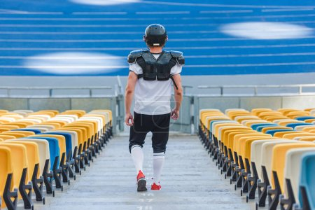 rear view of sportive american football player on stairs at sports stadium