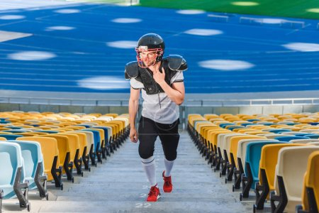 handsome young american football player going upstairs at sports stadium