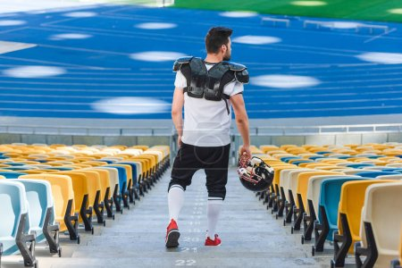 rear view of young american football player on stairs at sports stadium