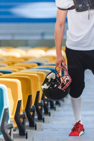 cropped shot of american football player standing on stairs at sports stadium