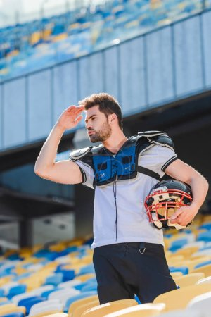 handsome young american football player in equipment standing on tribunes at sports stadium and looking away
