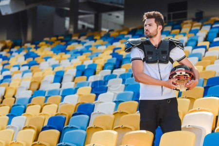 handsome young american football player in equipment standing on tribunes at sports stadium