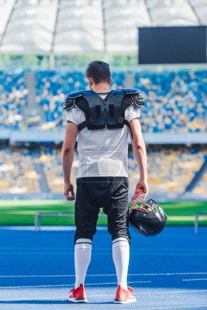rear view of american football player with helmet standing alone at sports stadium