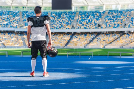 rear view of american football player standing alone at sports stadium