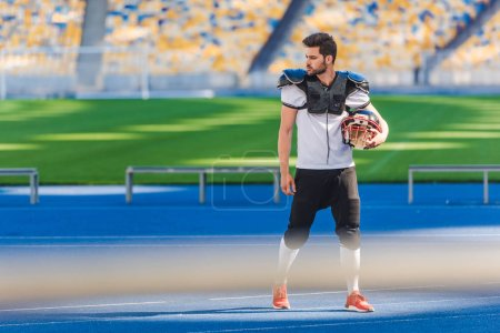 athletic american football player standing alone at sports stadium