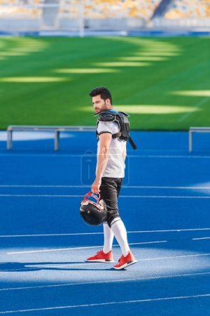 young american football player standing alone at sports stadium