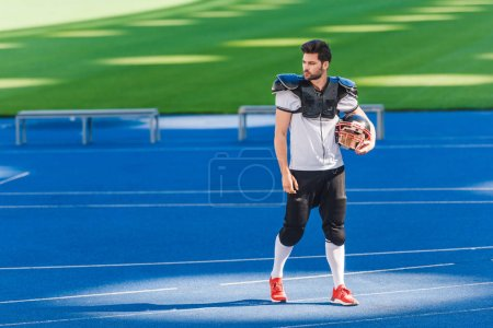 attractive young american football player standing alone at sports stadium