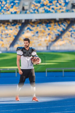 handsome young american football player standing alone at sports stadium