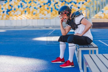 side view of young american football player holding cage of helmet while sitting at sports stadium