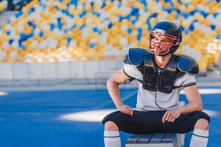 handsome young american football player sitting on bench at sports stadium