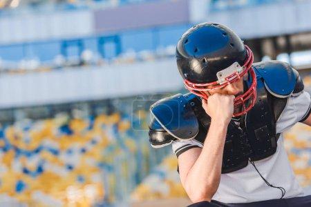 sad young american football player sitting at sports stadium