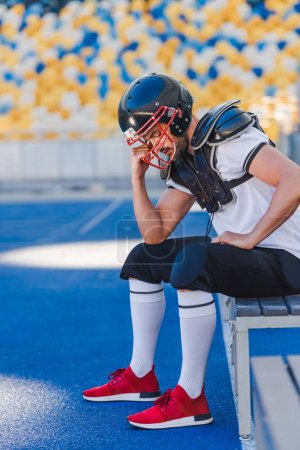 depressed young american football player sitting at sports stadium