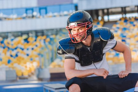 serious young american football player sitting at sports stadium