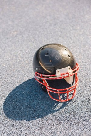 high angle view of american football helmet lying on asphalt
