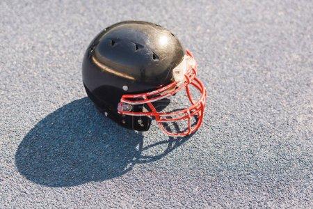high angle view of black american football helmet lying on asphalt
