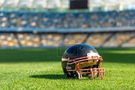 close-up shot of american football helmet lying on green grass of stadium