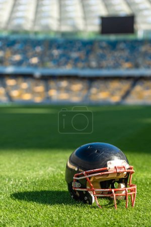 close-up shot of american football helmet lying on grass of stadium