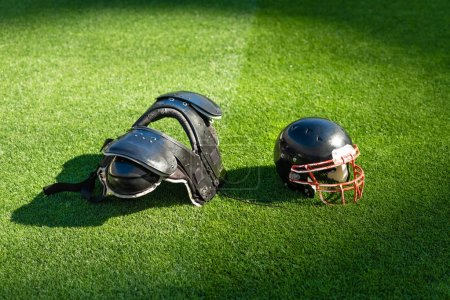 american football helmet with chest protection lying on grass