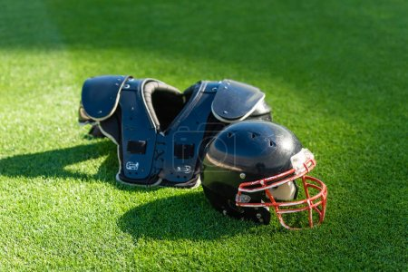 american football helmet with chest protection lying on green grass