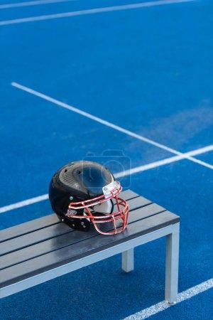 american football helmet lying on bench at stadium